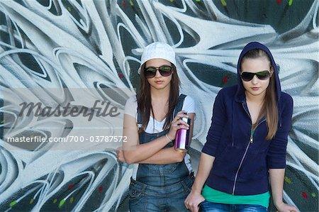 Jeunes filles tenant peut de peinture en aérosol devant mur couvert de Graffiti