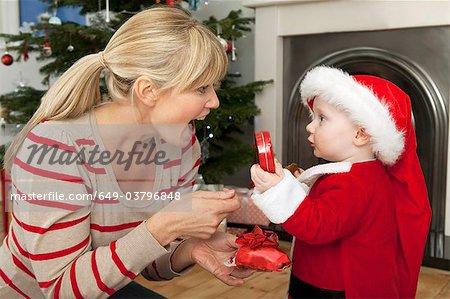 Eine Mutter gibt ihrem Sohn ein Weihnachtsgeschenk