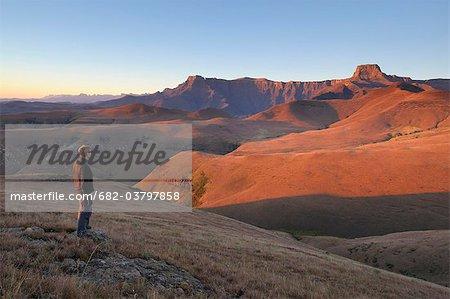 Randonneur avec vue sur la montagne de l'amphithéâtre à l'aube de Witsieshoek Royal Natal National Park, Ukhahlamba Drakensberg, Province de l'État libre, en Afrique du Sud