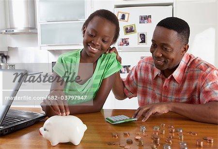 Vater Tochter Geld zählen und legen Sie in Johannesburg, Südafrika, Sparschwein helfen