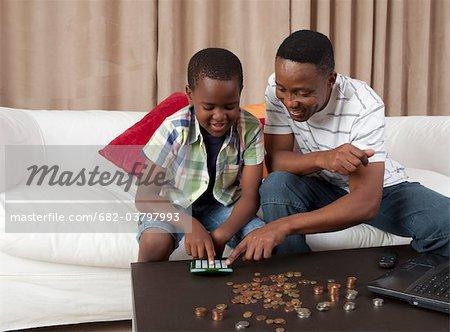 Mann hilft Sohn Graf Geld mit Rechner, Johannesburg, Südafrika