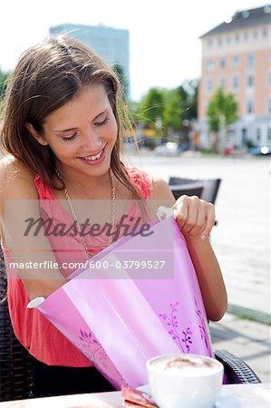 Jeune femme regardant dans le sac-cadeau