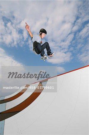 Junger erwachsener Mann springen beim Skateboarden