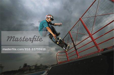 Asiatische Skateboarder in der Luft