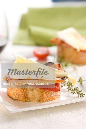 Épine dorsale de porc, le poivron rouge et Brie sur une tranche de bouchées de pain