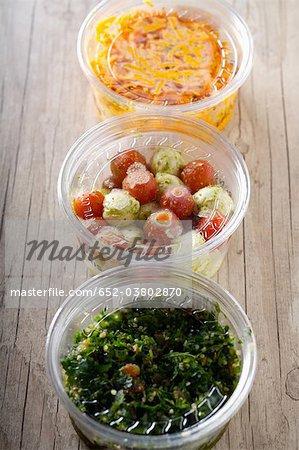 Taboulé libanais, tomates et mozzarella, râpé de carottes dans des contenants en plastique