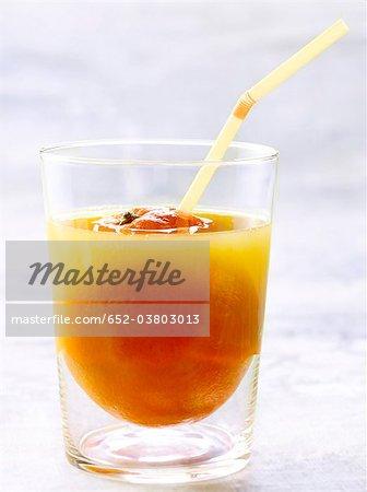 Glass of orange juice with a straw