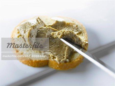 Anchoyade auf eine Scheibe Brot
