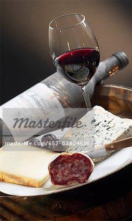 Assiette de fromage et saucisson, bouteille et verre de vin rouge