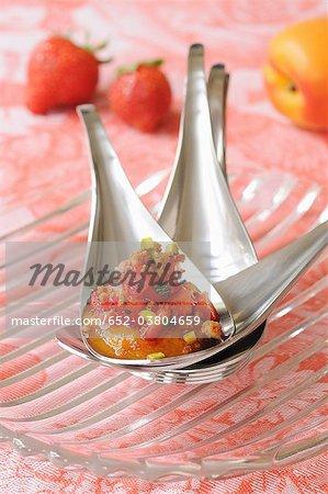 Cuillerée de compotes abricots avec des fraises en dés et coriandre