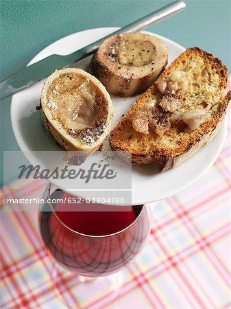 Knochenmark-Knochen auf Toast und ein Glas Rot Wein