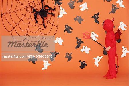 Junge, verkleidet als Teufel vor Orange Hintergrund