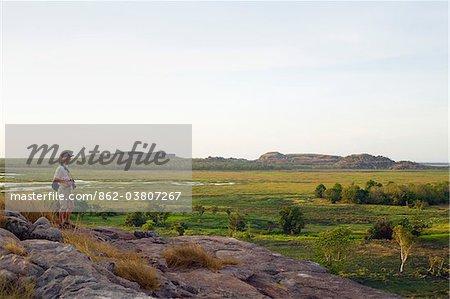 Australie, nord du territoire, le Parc National de Kakadu, Ubirr. Un randonneur surplombe la plaine d'inondation de Nadab au site sacré autochtone de Ubirr.