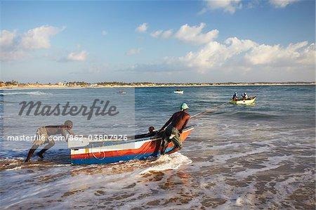 Fishermen launching fishing boats on Tofo beach, Tofo, Inhambane, Mozambique