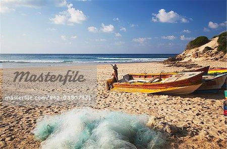 Woman sitting on fishing boat on beach, Tofo, Inhambane, Mozambique
