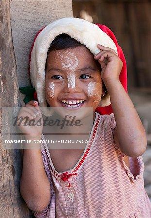 Myanmar, Birmanie, Mrauk U. village Esptein coiffé d'un chapeau de Noël, son visage décoré de thanaka, une crème solaire locale faite à partir d'écorce moulue, Mrauk U, l'état de Rakhine.