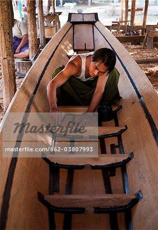 Myanmar, Inle-See. Ein Fischer Abdichtung eine neue Holzboot, Inle-See, Myanmar.