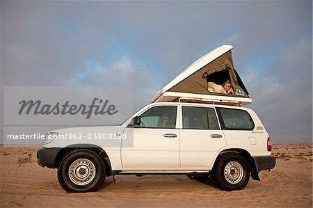 Oman, Wahiba Sands. Une jeune femme peeps hors de sa tente de toit au petit matin.