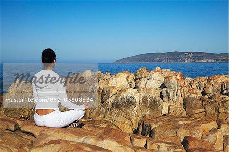 Woman practicing yoga on rocks, Plettenberg Bay, Western Cape, South Africa