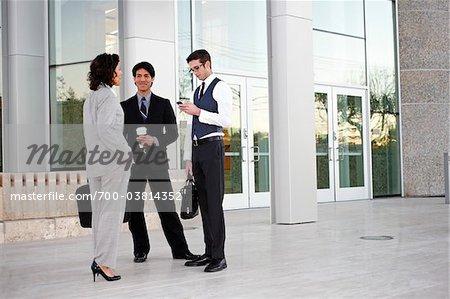 Parler à l'extérieur de l'immeuble de bureaux des gens d'affaires