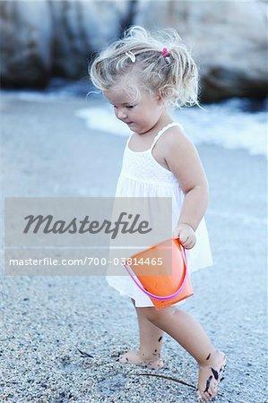 Petite fille avec godet à la plage