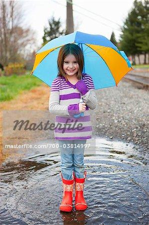Jeune fille debout dans une flaque d'eau tenir parapluie