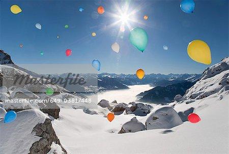 Ballons flying over winter landscape
