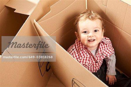 Petit garçon assis en cas d'emballage
