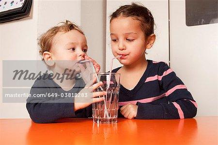 Garçon et fille l'eau potable avec pailles