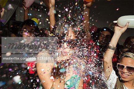 Menschen tanzen auf Party, Frau bläst glitter