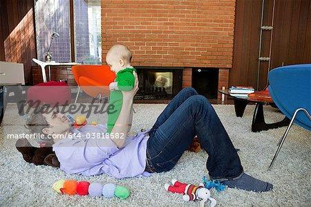 Père joue avec son bébé dans la salle de séjour