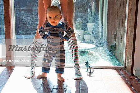 Mère aider les premiers pas de bébé fils prendre