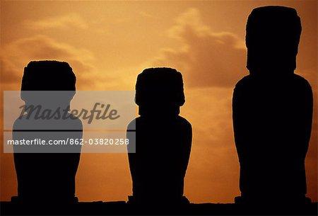 Trois des quinze colossales Pierre statues ou moais de Tongariki silhouetté sur la lumière de la lune montante.Les moaïs debout sur leur plate-forme ou ahu sur la côte orientale de l'île, au pied de la péninsule de Poike. Ahu Tongariki est la plus grande plate-forme de l'île à plus de 200 m de long et a la plupart IMAO.
