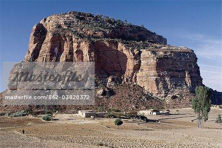 Près de Degum, les peuplements d'église de delporte rupestres au sommet d'un massif, qui fait partie des montagnes de Gheralta spectaculaire du Nord Ethiopia.A tigré homestead se trouve sur la plaine aride de Hawzien des centaines de mètres plus bas. Plats maisons en pierre avec toiture, qui sont communes dans la Province du Tigré, peuvent avoir été introduites en Éthiopie d'Arabie 700 ans avant j.-c..