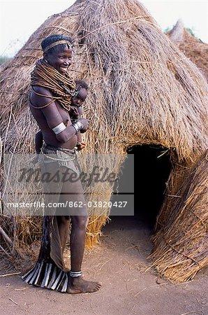 Une femme Nyangatom se tient avec son bébé sur la hanche à côté de sa hutte dans son camp temporaire. Nyangatom marié femmes jupes vêtements richement perlées qui atteignent le sol à l'arrière et souvent ont des panneaux de différente calkfskin coloré cousus dans la queue le Nyangatom ou Bume sont une tribu nilotique des bergers semi nomades qui vivent le long des rives du fleuve Omo dans le sud-ouest de l'Éthiopie.