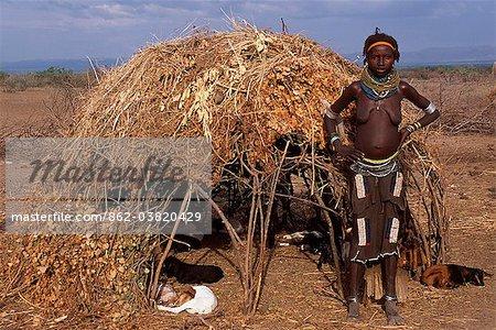 Une femme de Nyangatom porte plusieurs couches de perles de colliers, un jupe de veau finement perlée et bracelets métalliques, des amulettes et des bracelets de cheville. Elle se tient à côté d'une construction temporaire de ruche de bâtons, l'herbe et feuilles construits pour faire de l'ombre de ses chèvres. Le Nyangatom ou Bume sont une tribu nilotique de pasteurs semi-nomades qui vivent le long des rives du fleuve Omo dans le sud-ouest de l'Éthiopie