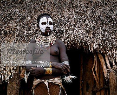 Un Karo femmes se tient dans l'embrasure de la porte à sa hutte dans le village de Duss. Une petite tribu Omotic associés à Hamar, qui vivent le long des rives du fleuve Omo en Éthiopie le sud-ouest, le Karo sont renommés pour leur peinture sur corps élaborés à l'aide de craie blanche, la pierre concassée et autres pigments naturels. En plus de son visage, elle a décoré son corps avec verticilles de poil de chèvre attaché par cuir co