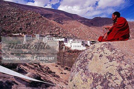 Monastère de Drepung. Un moine repose parmi les rochers peints dans les collines à côté de ce vaste complexe. Fondée au XVe siècle, apogée de Drepungs est venu deux siècles plus tard, quand il avait environ 10 000 moines affiliés de plus de 300 monastères de direction de l'école Gelugpa.