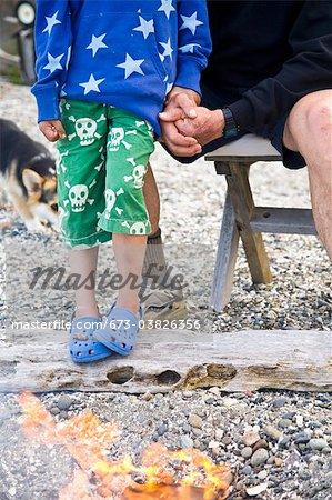 garçon et homme près de feu de plage