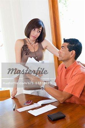 femme se tenant près de payer les factures de l'homme