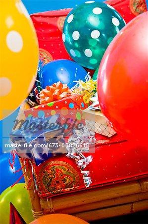 Roter Stuhl mit Geschenke und Ballons