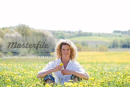 A woman sitting in a field of dandelions, Sweden.
