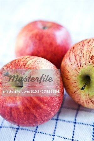 Drei Äpfel auf Küchentuch.