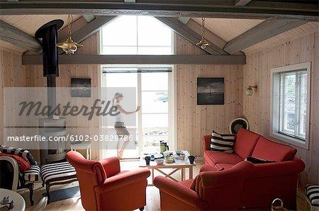 Eine Frau in einem Wohnzimmer stehen am Fenster, Lofoten Inseln, Norwegen.