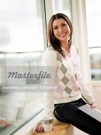 Frau holding Datei und Cup, sitzen, Lächeln