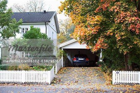 Eine Garage mit einem geparkten Auto durch ein weißes Haus, Schweden.