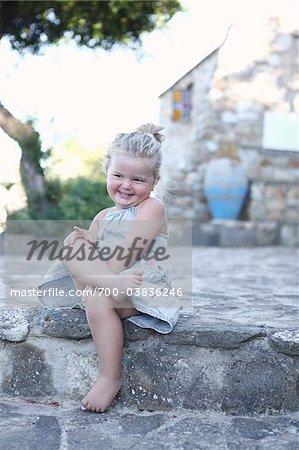 Petite fille assise les jambes croisées