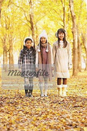 Trois filles debout dans le parc à l'automne