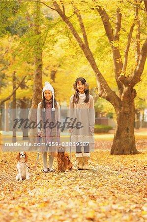 Filles avec leurs chiens dans le feuillage d'automne