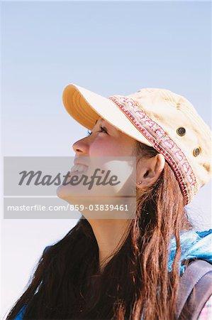 Jeune femme souriante et regardant vers le haut dans le ciel